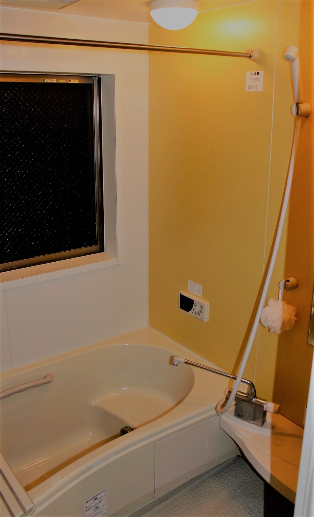 Modern Japanese shower hose with tub beside it and water heater remote on wall.