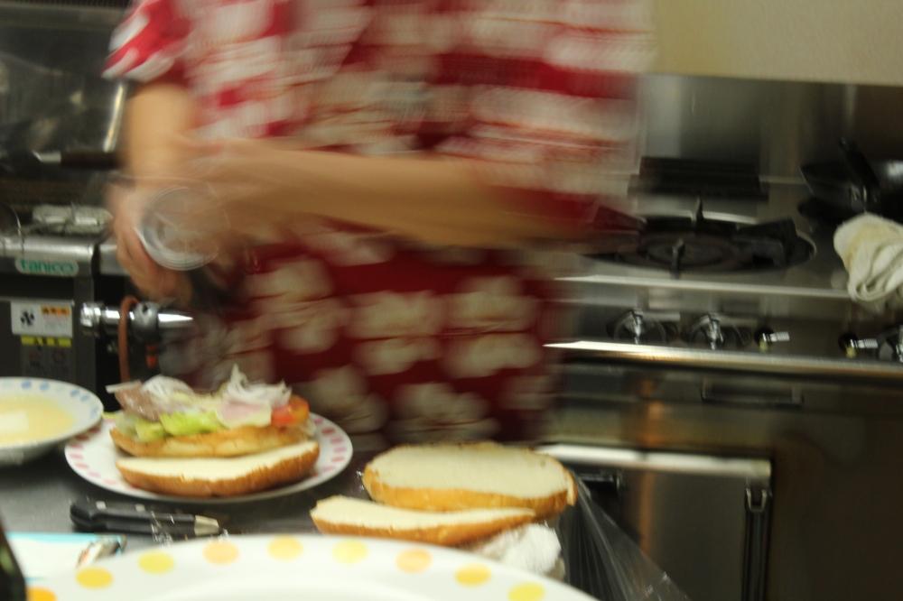 Round Hibiscus Robed Hawaiian making burgers.JPG
