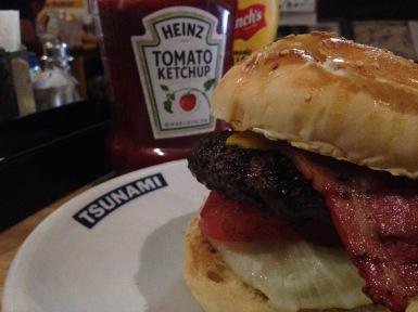tsunami bacon cheese burger, ketchup and mustard in the back