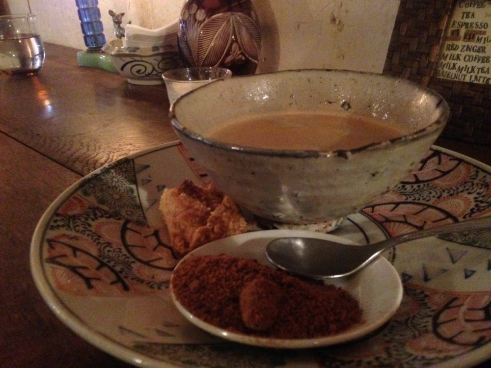 Bowl of black coffee from cafe antique with milk and sugar and cookie